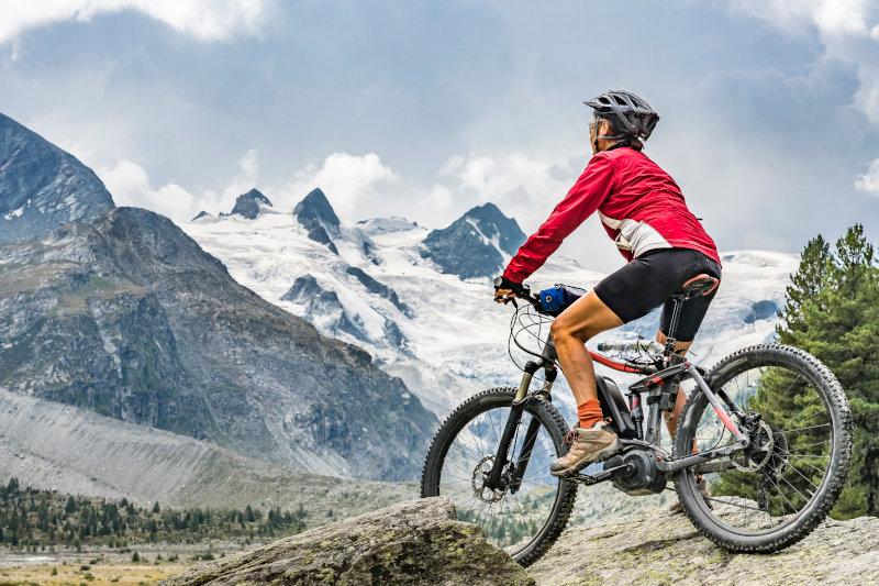 Ciclista con ebike in montagna