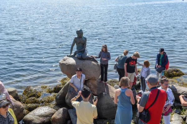 Turisti che fanno foto ricordo accanto alla statua della Sirenetta a Copenhagen